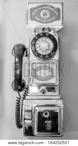 Vintage, out of service, chrome plated, older style, coin operated, public, pay telephone from an earlier time in technology.  In black & white.