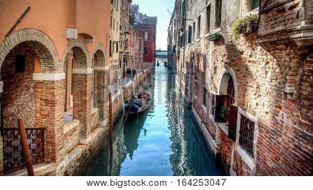 Venice, Italy - February 17, 2015:  Classical picture of the venetian canals with gondola across the canal.