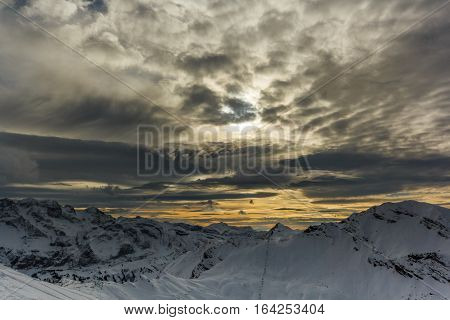 Stormy clouds over a snowcaped mountain range with yellow sky