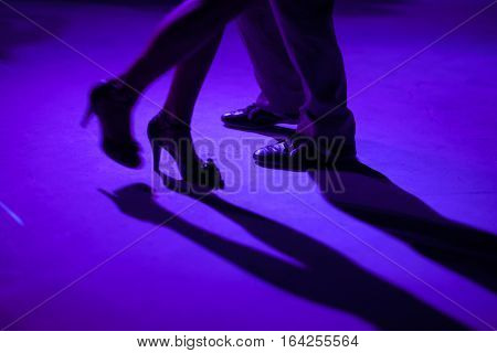 Tango dancers in milonga ballroom detail of shoes.