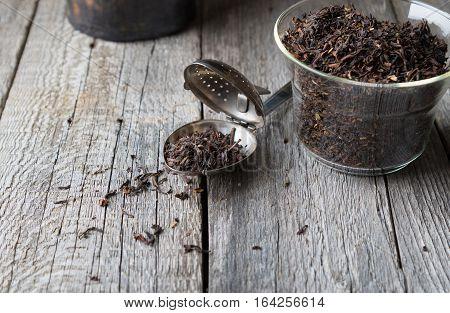 Tea brews and strainer on rustic vintage grey boards