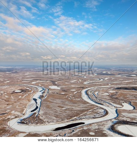 Aerial view of forest-tundra and small river during a winter day.