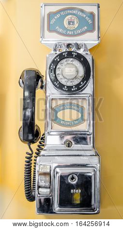Vintage, out of service, chrome plated, older style, coin operated, public, pay telephone from an earlier time in technology.