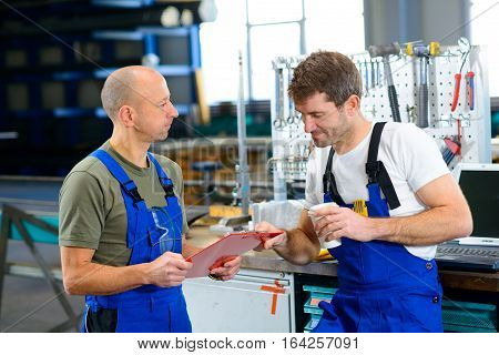 Two Worker In Factory In Conversation