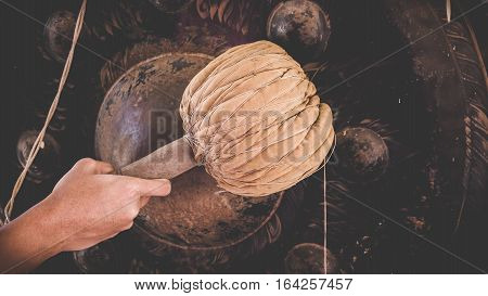 Hand of Asian young man hit big gong or Thai instrument in temple for pray. Thai instrument concept.