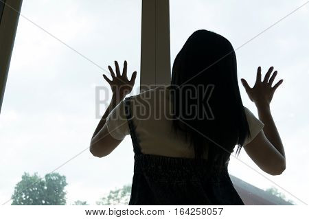 Woman sitting strain ,unhappy In the corner on the bow the knee In the corner of the room, even when the light shines