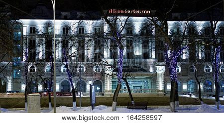 Ulyanovsk Russia - January 03 2017: Building of hotel Hilton Garden Inn in the winter evening. Hotel and trees decorated with festive holiday illumination lights.
