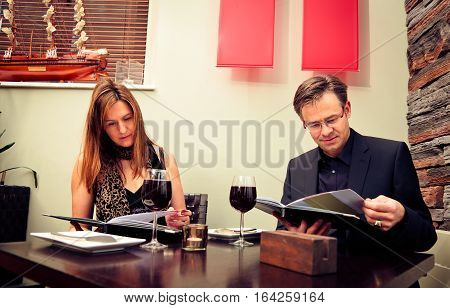 adult couple reading the menu in a restaurant