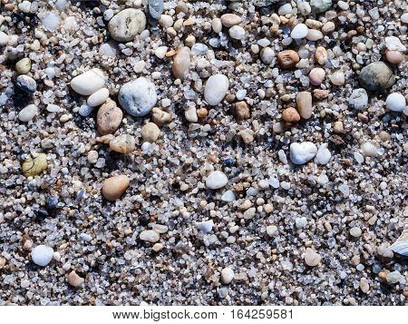 Small rounded stones smoothed by the sea along the shoreline in Sandy Hook New Jersey.
