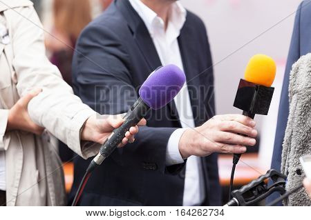 Journalists holding microphones, conducting media interview. News conference.