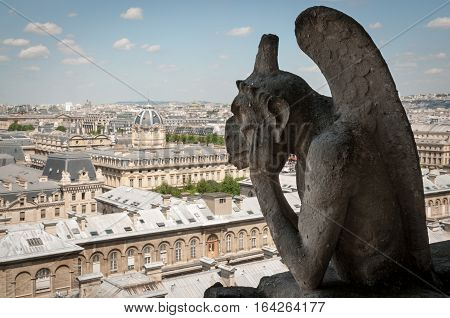 Gargoyle of Notre Dame de Paris overlooking the city
