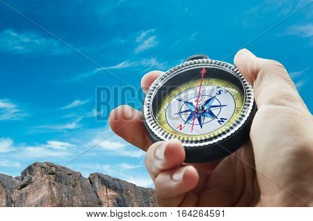 a compass in the hand in mountains