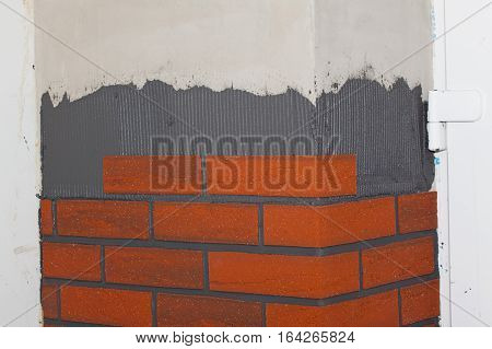 Reconstruction of the house. Bonding of brick tiles on the walls. Imitation brick.