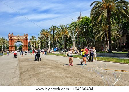 Barcelona, Spain - May 27, 2016: many tourists near the Arc de Triomphe in sunny summer day,  Artist blow bubbles in the alley