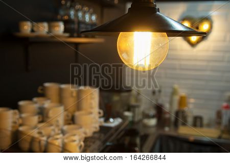 Edison's light bulb and lamp in modern style. Warm tone light bulb lamp. Lamps in coffee shop. Edison's lightbulb in interior.