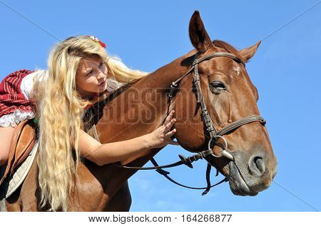 teenage girl with long hair horseback riding in sunny day