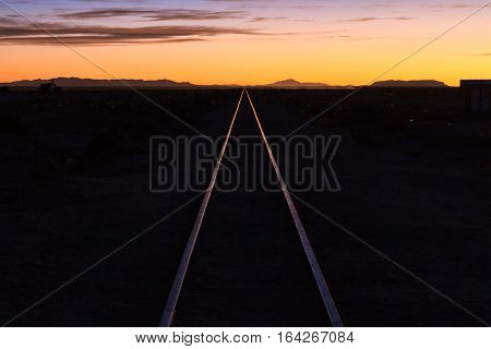 Rail track through the desert at sunset Uyuni Bolivia