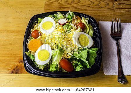 fresh garden salad of lettuce tomato radish carrot cheese and egg on wood background