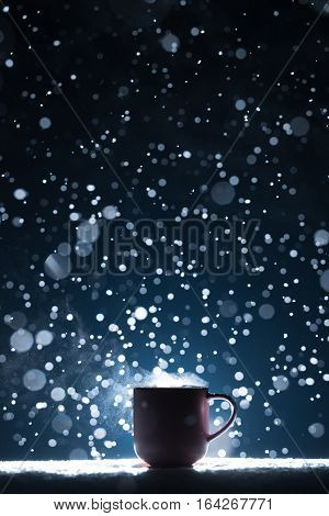 backlighted cup of hot coffee on night snowy background; mug with warm tea in snow winter weather;
