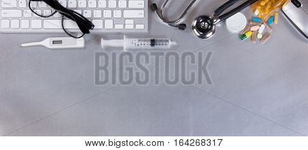 Stainless steel medical doctor table desk with computer keyboard stethoscope thermometer medicine mouse and syringe. Flay layout.
