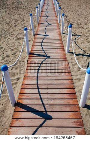 Wooden walkway over the sand dunes to the beach. Beach pathway in Lido di Ostia ( Lido di Roma) private beach Salvataggio Italy.