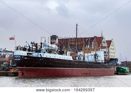 POLAND GDANSK - DECEMBER 18 2011: View of the ship-museum freighter Soldek near historic buildings of the island Olowianka. Soldek was the first ship built in Poland after World War II in 1948.