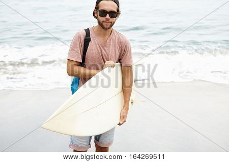 Cheerful Young Bearded Tourist In Sunglasses Holding Bodyboard And Looking At Camera With Pleased Sm