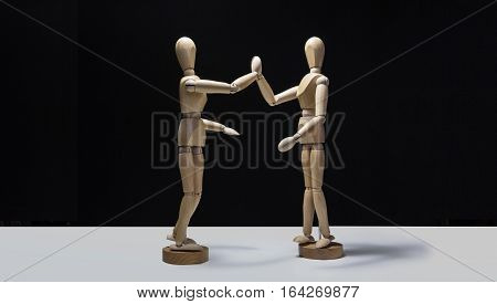 Wooden Mannequins-hi5 side 01 - Two wooden mannequin's high fiving. Shot from the side showing full body profiles.