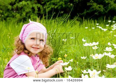 Happy kid on the meadow with white flowers