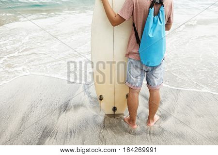 Rear Portrait Of Surfer Standing Barefooted On Beach In Sea Water, Carrying Bag On His Shoulders, Ho