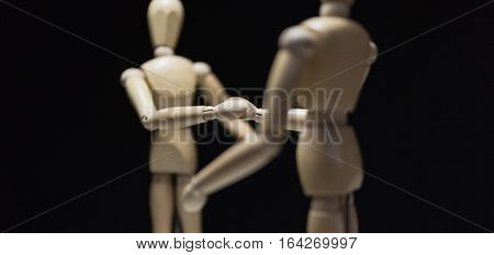 Wooden Mannequins-shaking close-focusBlur - Two wooden mannequin's shaking hands. Shot close in with focus blur and from behind the right mannequin.