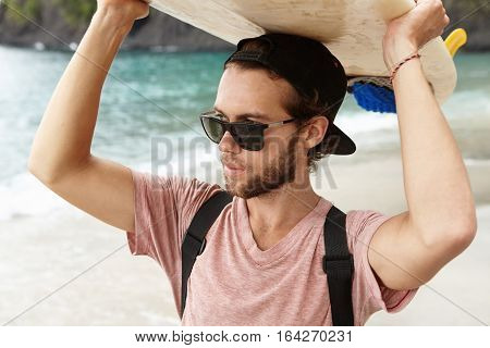 Attractive Young Bearded Surfer In Shades Standing On Beach At Ocean, Holding Surfboard On His Head