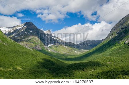 Green valley surrounded by mountains on the road to Trollstigen. Norway canyon landscape.