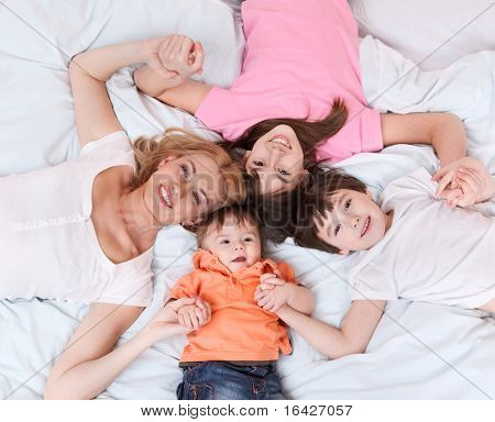 Happy mother and cheerful kids lying on bed and holding hands