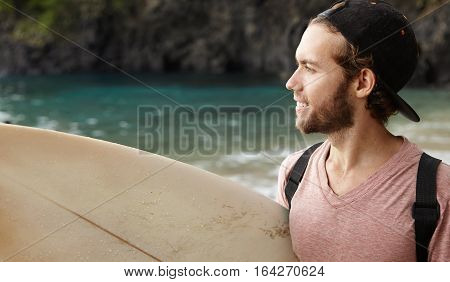 Profile Portrait Of Surfer Man In Good Mood, Carrying His Surfing Board Under His Arm Looking At Sea