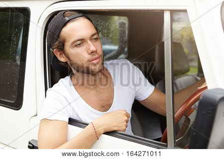 Young Bearded Adventurer Wearing Black Snapback Driving His White Suv, Going To Safari Trip, Stickin