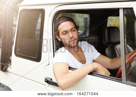 People, Leisure, Travel And Vacations Concept. Fashionable Unshaven Man Wearing Snapback Driving His