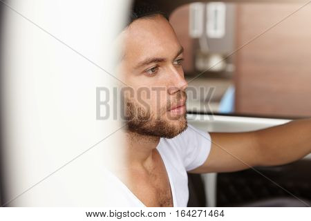 Side View Of Attractive Hipster With Beard Sitting Inside His White Automobile While Driving To Nati