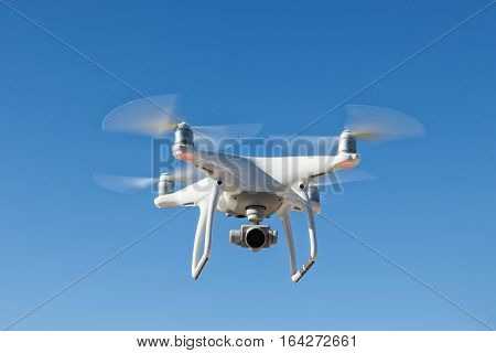 White quadrocopter hovers in the sky. Modern technology photo and video shooting.