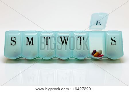 Pill box with Friday's pills visible on white background.