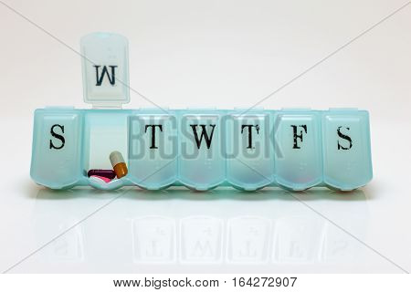 Pill box with Monday's pills visible on white background.