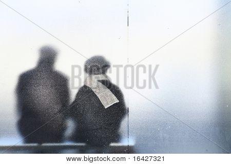 Casal velho sentado em uma parada de ônibus.
