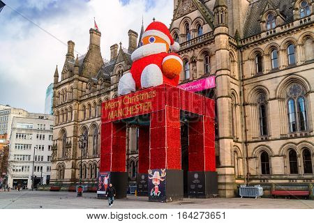 MANCHESTER, UK - DECEMBER 26: Historic Manchester Town Hall Designed by architect Alfred Waterhouse decorated for festive season with a figure of Father Christmas. Manchester December 26, 2016.