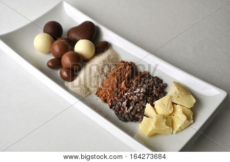 Ingredients for making chocolate - raw cacao butter, cocoa powder, crushed cacao beans, nibs, cane sugar, and chocolates