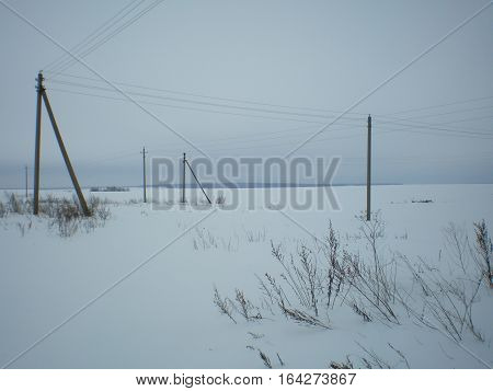 Power transmission pole with wires in the background of a winter field and forest winter snow nature electricity С Power,background,field,forest,pole,transmission,winter,wires,Столбы ЛЭП на фоне зимнего поля и леса