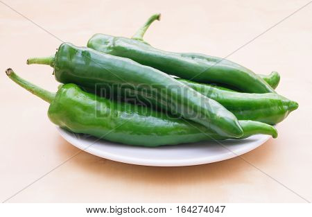 Green vegetables. Organic long green peppers on white plate selective focus horizontal
