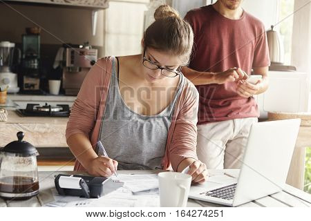 Beautiful Young Woman In Spectacles Looking Serious Writing Down With Pen While Managing Taxes And C