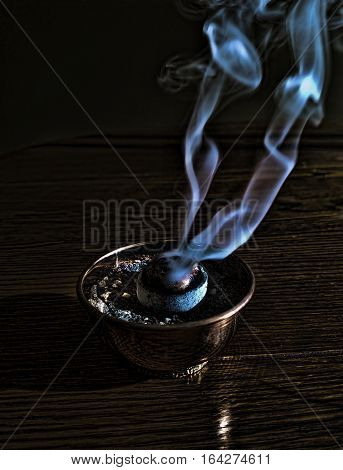 Incense smoke plumes rising from incense burner