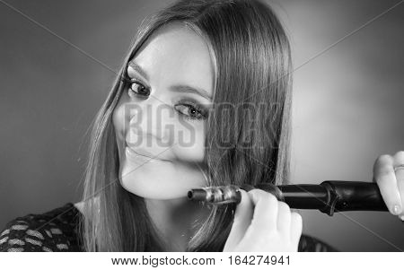 Haircare hairstyiling at home concept. Happy woman curling her long brown hair with curler. Black and white shot.