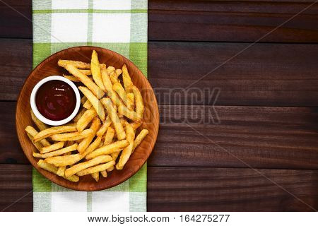 Fresh homemade crispy French fries with a small bowl of ketchup on wooden plate photographed overhead on dark wood with natural light